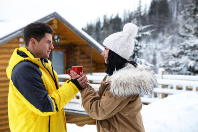 Happy couple with hot drink at resort. Winter vacation