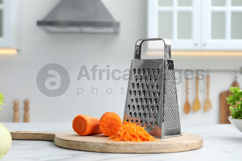 Grater and fresh ripe carrot on white table in kitchen. Space for text