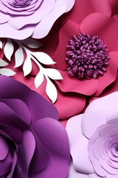 Different beautiful flowers and branches made of paper as background, top view