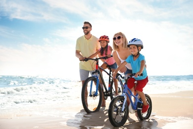 Happy parents teaching children to ride bicycles on sandy beach near sea