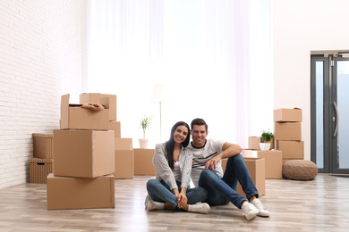 Happy couple in room with cardboard boxes on moving day