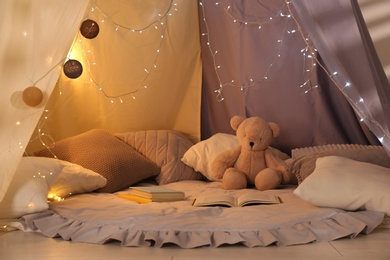 Play tent with books, pillows and Teddy bear. Modern children's room interior