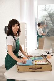 Professional janitor with organizer and cleaning supplies at table in office