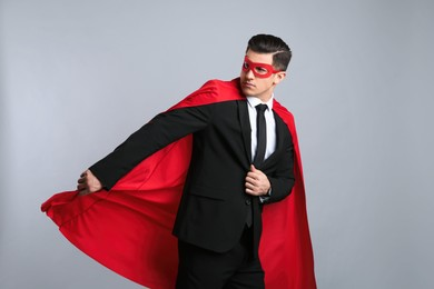 Businessman wearing superhero cape and mask on grey background