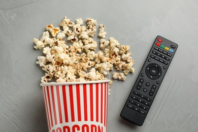 Modern tv remote control and popcorn on grey table, flat lay