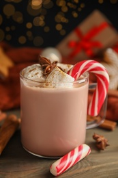 Glass cup of tasty cocoa with marshmallows and Christmas candy cane on wooden table