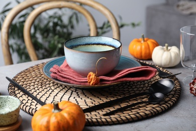 Seasonal table setting with pumpkins and other autumn decor in dining room