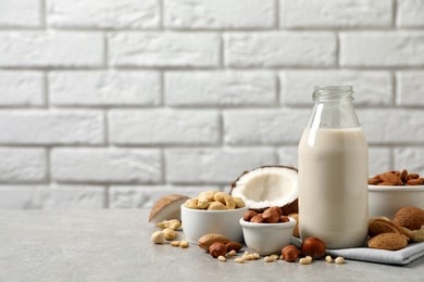 Vegan milk and different nuts on light table. Space for text