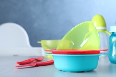 Bright child's dishware on grey table indoors. Space for text