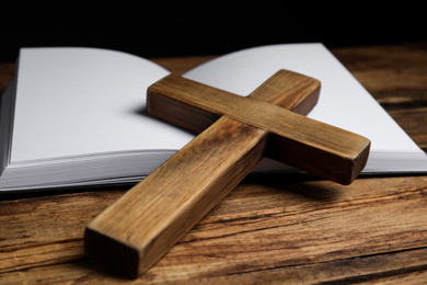 Christian cross and Bible on wooden background, closeup. Religion concept