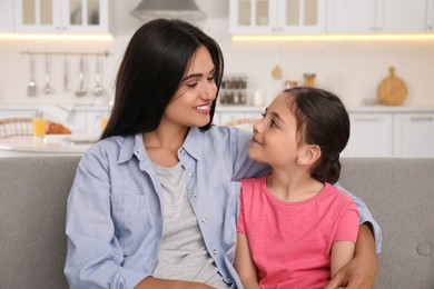 Happy mother and daughter on sofa at home. Single parenting