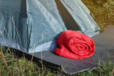 Red sleeping bag near camping tent on green grass outdoors