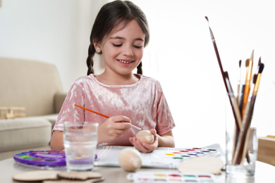 Little girl painting decorative egg at table indoors. Creative hobby