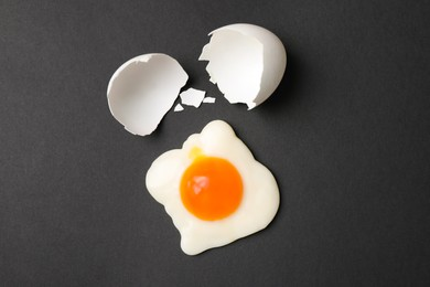 Sweet gummy fried egg and broken shell of real one on black background, flat lay. April Fools' Day
