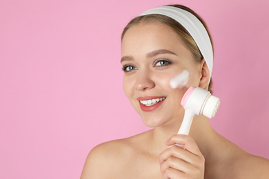 Young woman washing face with brush and cleansing foam on pink background. Cosmetic products
