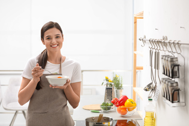 Young woman eating tasty vegetable soup in kitchen