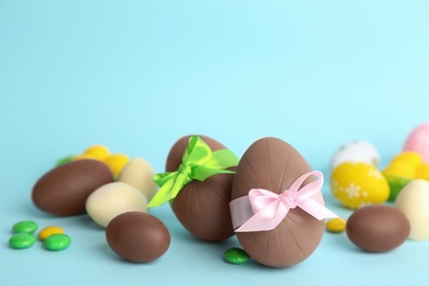 Sweet chocolate eggs and bright candies on light blue background. Space for text