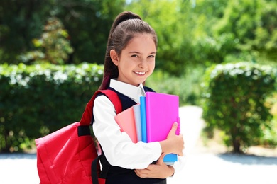 Cute little girl in school uniform with backpack and stationery on street