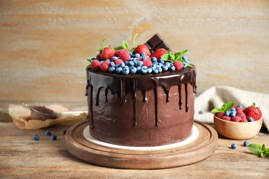 Freshly made delicious chocolate cake decorated with berries on wooden table
