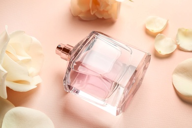 Bottle of perfume, beautiful flowers and petals on beige background