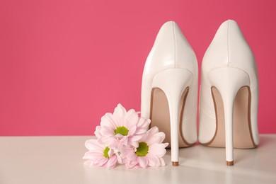 Beautiful tender flowers and woman's shoes on white table. Space for text