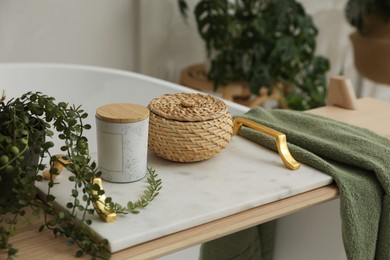 Tray with jar, wicker box, towel and green plant on bathtub indoors. Interior element