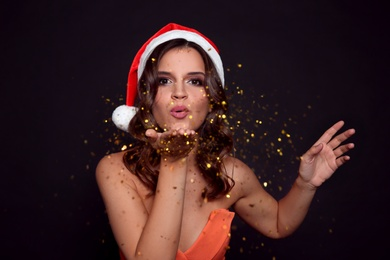 Beautiful woman in Santa hat blowing glitter on black background. Christmas party