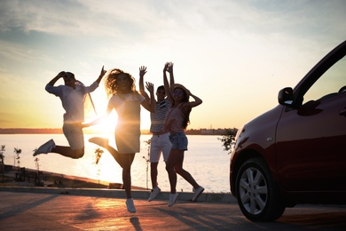 Happy friends jumping near car outdoors at sunset. Summer trip