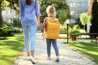 Young mother taking her little child to school through park