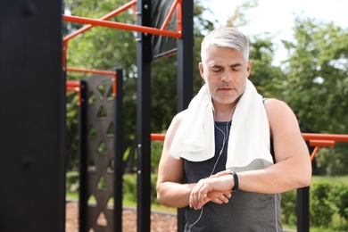 Handsome mature man looking at fitness tracker on sports ground, space for text. Healthy lifestyle