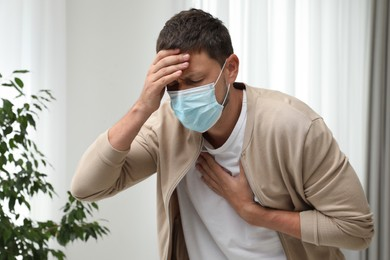 Man in medical mask suffering from pain during breathing indoors