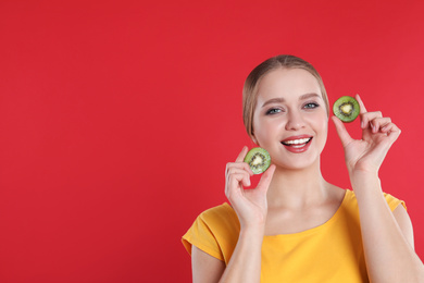 Young woman with cut kiwi on red background, space for text. Vitamin rich food