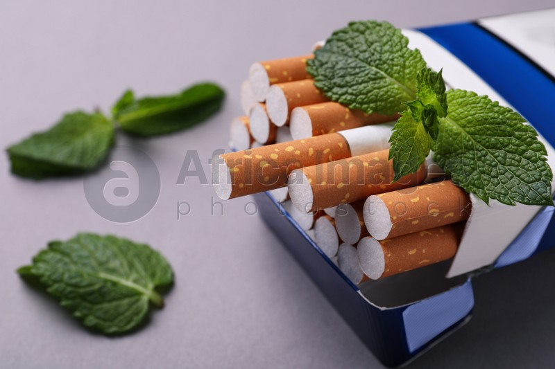 Pack of menthol cigarettes and mint leaves on grey background, closeup