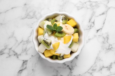 Delicious fruit salad on white marble table, top view