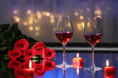 Glasses of wine, candles and roses on table against blurred lights. Romantic dinner for Valentine's day