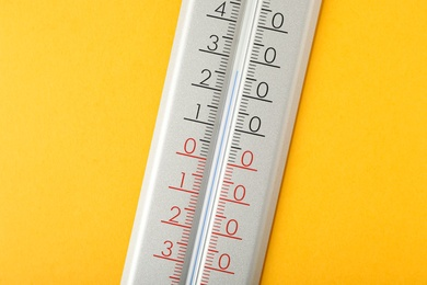 Modern weather thermometer on yellow background, closeup