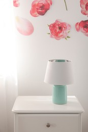 Lamp on nightstand near floral wall indoors. Interior design