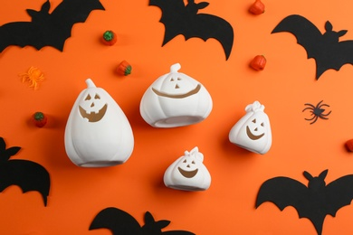 White pumpkin shaped candle holders, jelly candies, decorative bats and spiders on orange background, flat lay. Halloween celebration