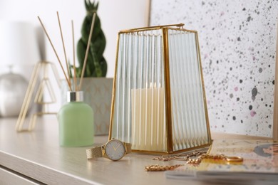 Beautiful holder with burning candle and stylish accessories on table indoors