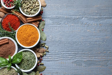 Different natural spices and herbs on grey wooden table, flat lay. Space for text