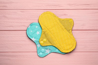 Reusable cloth menstrual pads on pink wooden table, flat lay
