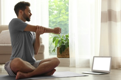 Man practicing yoga while watching online class at home during coronavirus pandemic. Social distancing