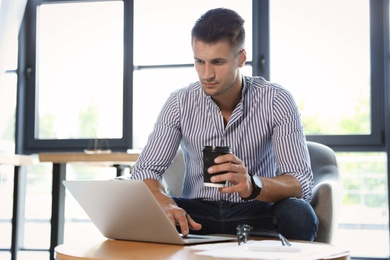 Male business trainer working with laptop in office