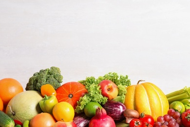 Assortment of fresh organic fruits and vegetables on light background, closeup. Space for text