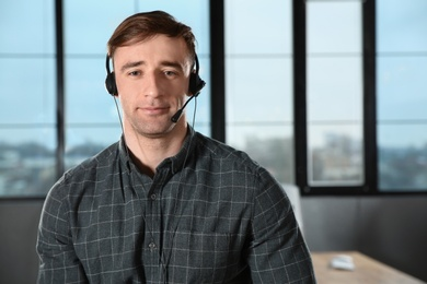 Male technical support operator with headset in office. Space for text