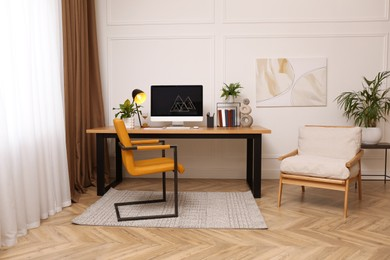 Room interior with comfortable workplace. Modern computer on wooden desk