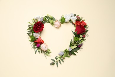 Beautiful heart made of different flowers on beige background, flat lay. Space for text