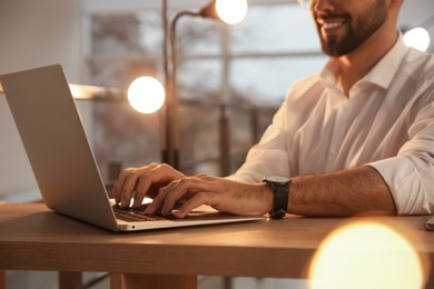 Man working with laptop at table in office, closeup