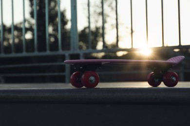 Modern pink skateboard with red wheels on top of ramp outdoors at sunset