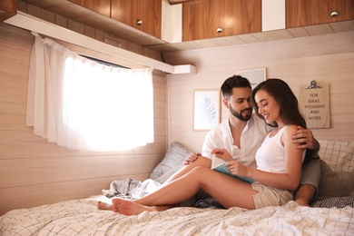 Happy young couple reading book on bed in trailer, space for text. Camping vacation